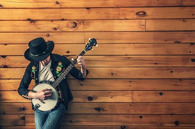 hudebník před dřevěnou stěnou